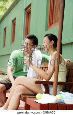 Couple in tennis outfit, sitting on bench on tennis court - Stock Photo