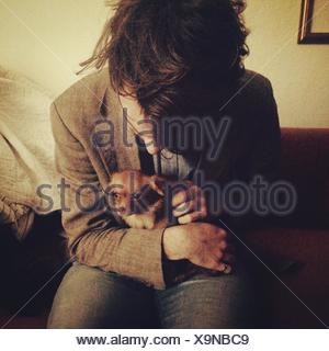 Young Man Petting Chihuahua Sitting In Lap - Stock Photo
