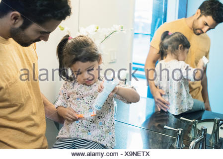 Father and daughter in bathroom brushing teeth - Stock Photo