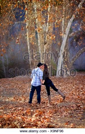 Couple walking away in a forest, playfully kissing - Stock Photo
