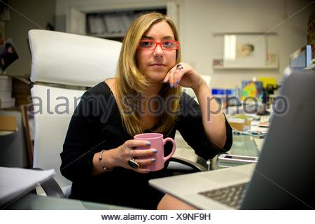 Portrait of young woman in office, sitting at desk, holding coffee cup - Stock Photo
