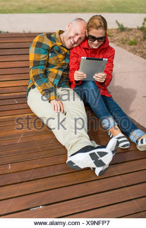 Australia, Queensland, Mid adult couple using digital tablet - Stock Photo