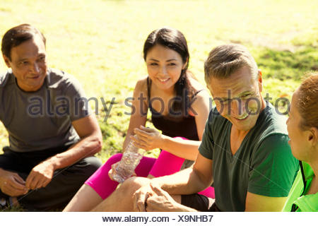 Four mature male and female runners taking a break in park - Stock Photo