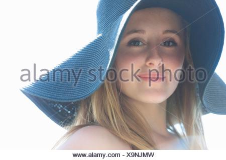 Portrait of teenage girl wearing blue sunhat - Stock Photo