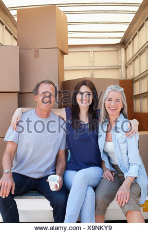 Friends sitting on back of moving van - Stock Photo