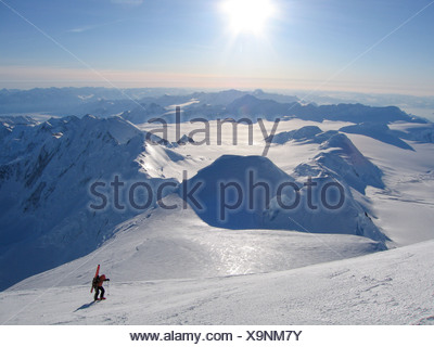 A ski mountaineer ascends the upper reaches of Mount Marcus Baker, the highest peak in the Chugach mountains, in the winter. - Stock Photo