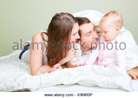 young family lying in bed with little daughter - Stock Photo