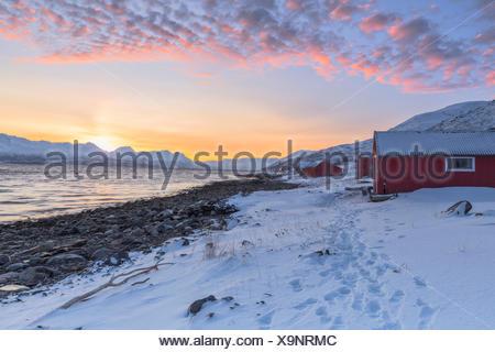 Sunset among the fishermen's houses overlooking the fjord. Nordmannvik, Kafjord, Lyngen Alps, Troms, Norway, Lapland, Europe. - Stock Photo