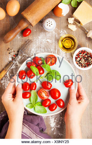 Hands of woman cooking italian food (Parmigiano, tomato, basil, olive oil) on rustic background. Top view - Stock Photo