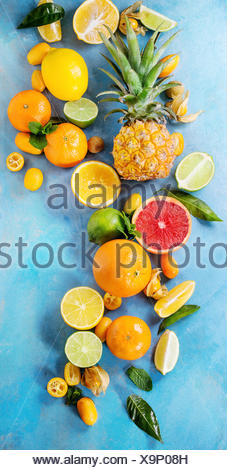 Variety of whole and sliced citrus fruits pineapple, grapefruit, lemon, lime, kumquat, clementine and physalis with mint over blue wooden background. - Stock Photo