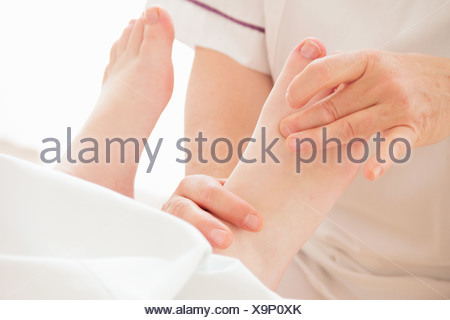 Woman having foot massage in spa - Stock Photo