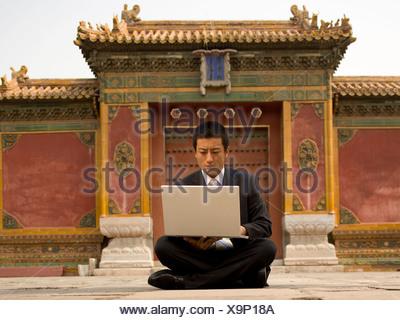 Businessman sitting cross legged outdoors with laptop - Stock Photo