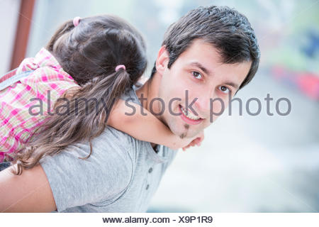 Side view portrait of young man piggybacking little daughter at home - Stock Photo