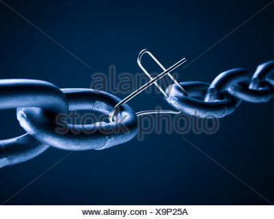Chain linked with broken paper clip against blue background - Stock Photo