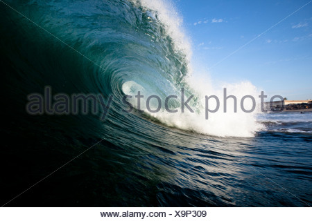 A large wave breaks close to shore. - Stock Photo