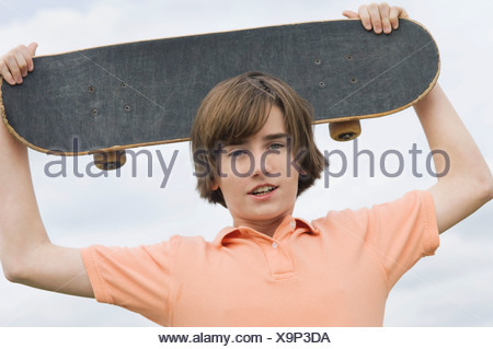 Portrait of a boy holding a skateboard over his head - Stock Photo
