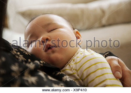 Close up of baby girl sleeping in mothers arms - Stock Photo