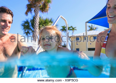 Parents swimming with toddler in pool - Stock Photo