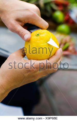 Close up of womans hands peeling lemon - Stock Photo