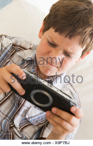 Young boy with handheld game indoors looking unhappy - Stock Photo