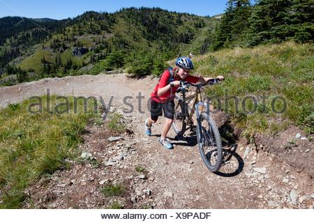 A teenage girl pushes her mountain bike in Whitefish, Montana. - Stock Photo