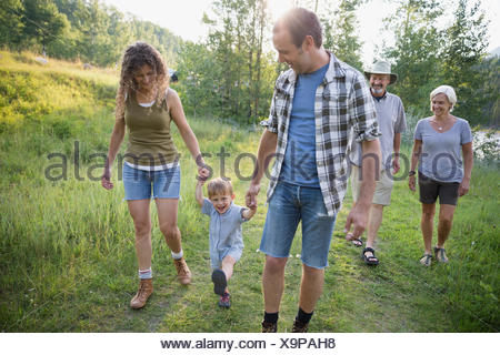 Multi-generation family walking in woods - Stock Photo
