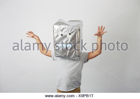 Portrait of boy with silver box on head, funny face on box - Stock Photo