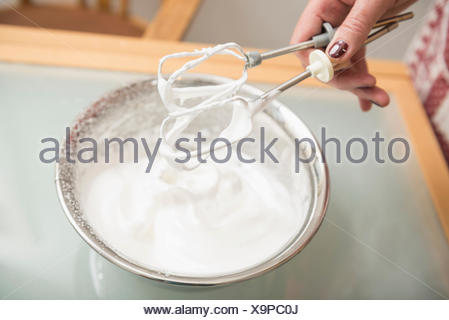 Senior woman holding wire whisk over meringue filled bowl, Munich, Bavaria, Germany - Stock Photo