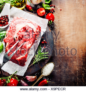 Raw beef steak with meat fork and ingredients on wooden background - Stock Photo