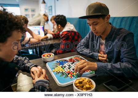 Tween boy friends playing Chinese checkers at cafe table - Stock Photo