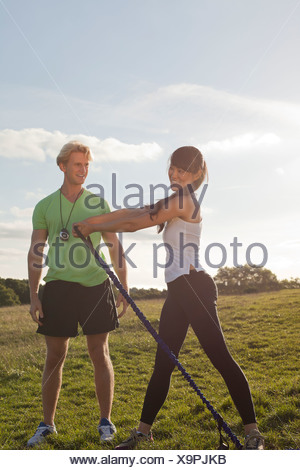 Personal trainer and female client doing stretch exercise - Stock Photo