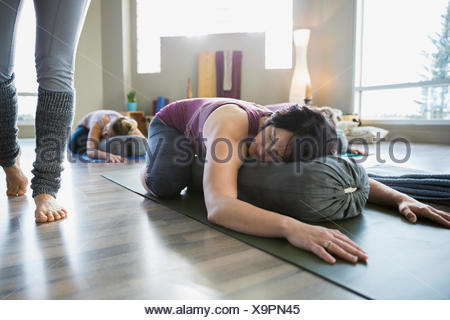 Woman using bolster in restorative yoga childs pose - Stock Photo