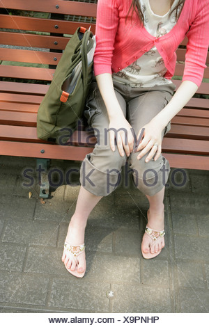 High angle view of hands and legs of a young woman sitting on the bench - Stock Photo