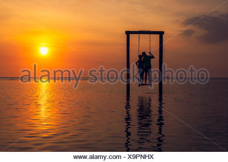 Silhouette of Man and woman kissing, standing on a swing in sea at sunset, Indonesia - Stock Photo