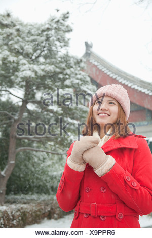 Young Woman Holding hands in snow - Stock Photo