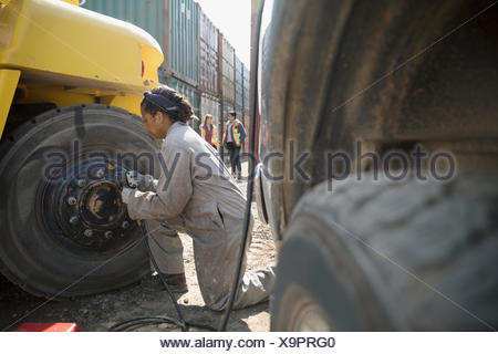 Female mechanics fixing heavy machinery in sunny industrial container yard - Stock Photo