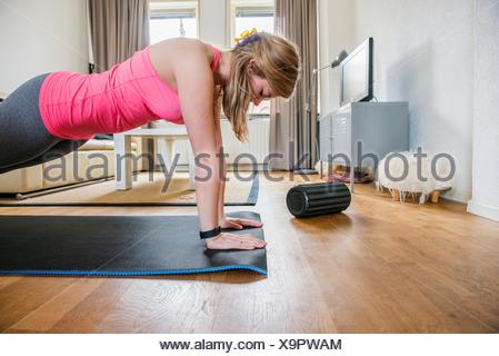 Tilburg, Netherlands. Young adult girly woman working out inside her living room. - Stock Photo