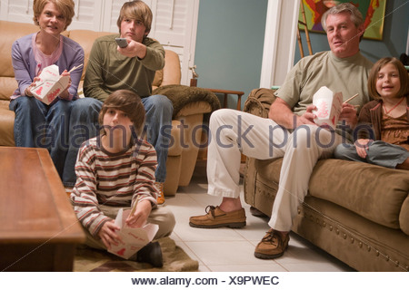 Family eating Chinese takeout dinner on couch watching TV - Stock Photo