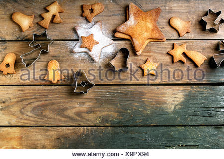 Homemade Christmas shortbread star shape sugar cookies different size with sugar powder and cookie cutters on old wooden surface - Stock Photo
