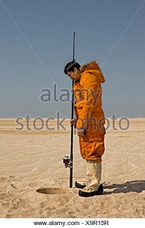 Eskimo fishing in desert - Stock Photo
