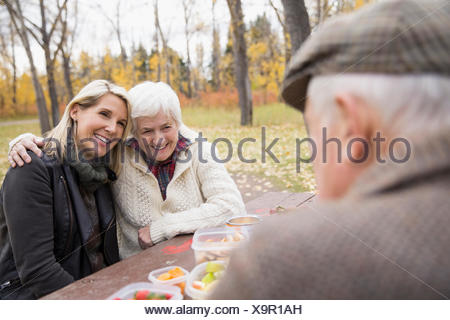 Mother and daughter hugging enjoying picnic at table in autumn park - Stock Photo