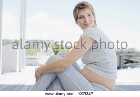 Pregnant woman sitting on deck - Stock Photo