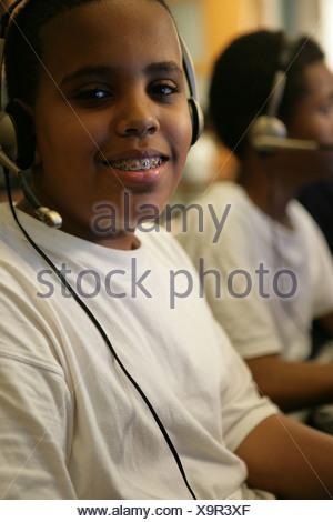 Boys (11-13) wearing headphones, portrait - Stock Photo