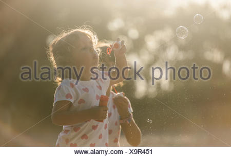Two little sisters making soap bubbles in the park at twilight - Stock Photo