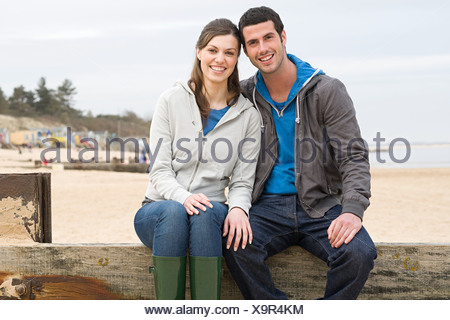Couple sitting on a fence at the beach - Stock Photo