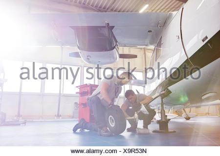 Male mechanics fixing wheels on airplane in hangar - Stock Photo