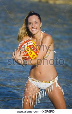 Attractive young woman on beach is catching a ball - Stock Photo