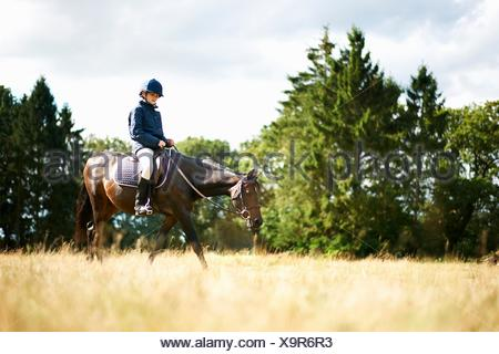 Girl horseback riding in field - Stock Photo