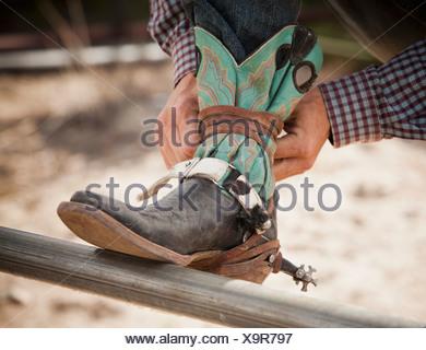 USA, Utah, Highland, Close-up of cowboy tying shoe - Stock Photo