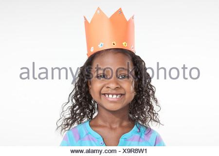Girl wearing orange paper crown - Stock Photo